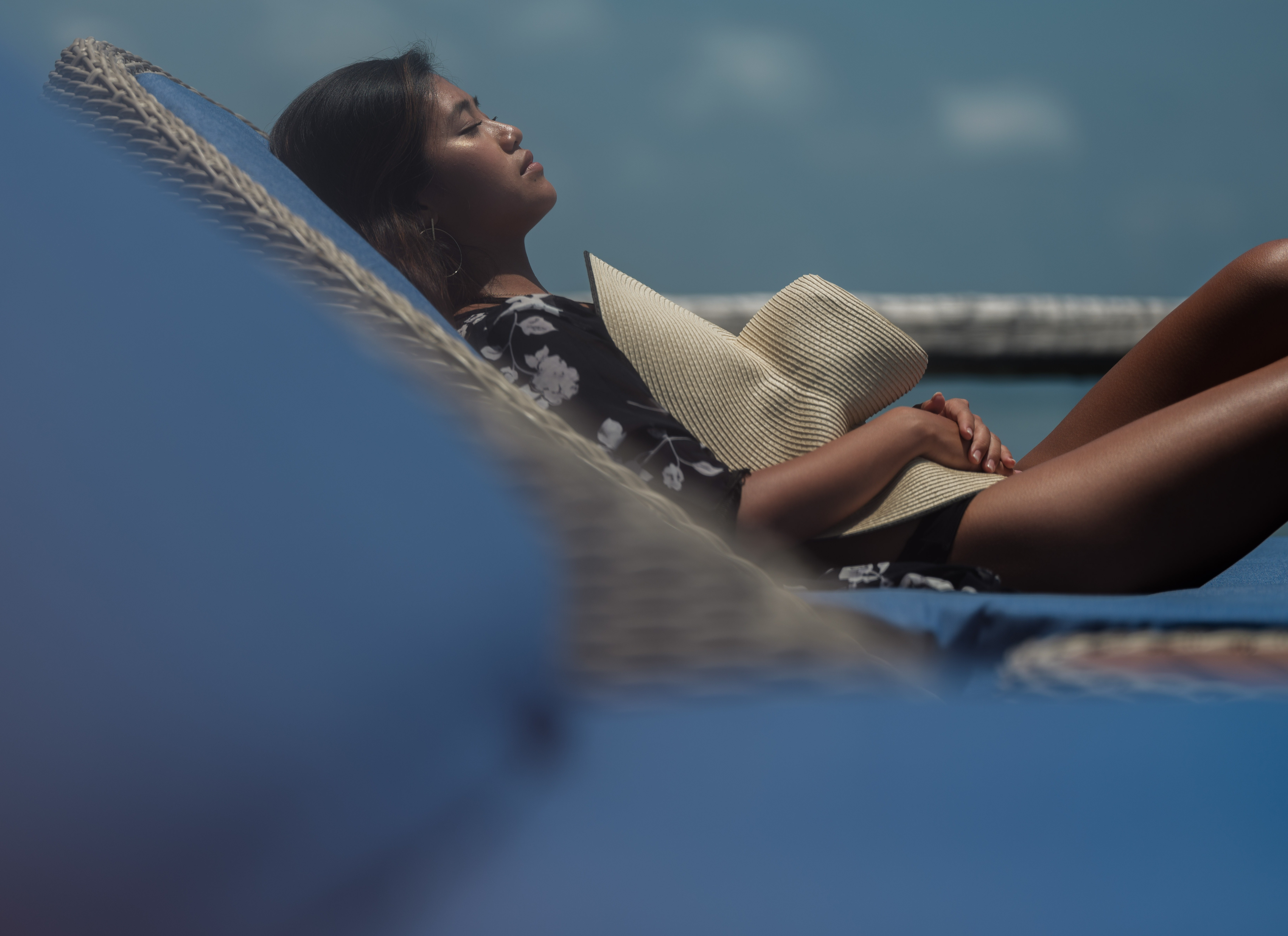 close_up_asian_girl_black_robe_holds_straw_hat_sun_bathing_on_blue_day_bed_overwater_suite-1