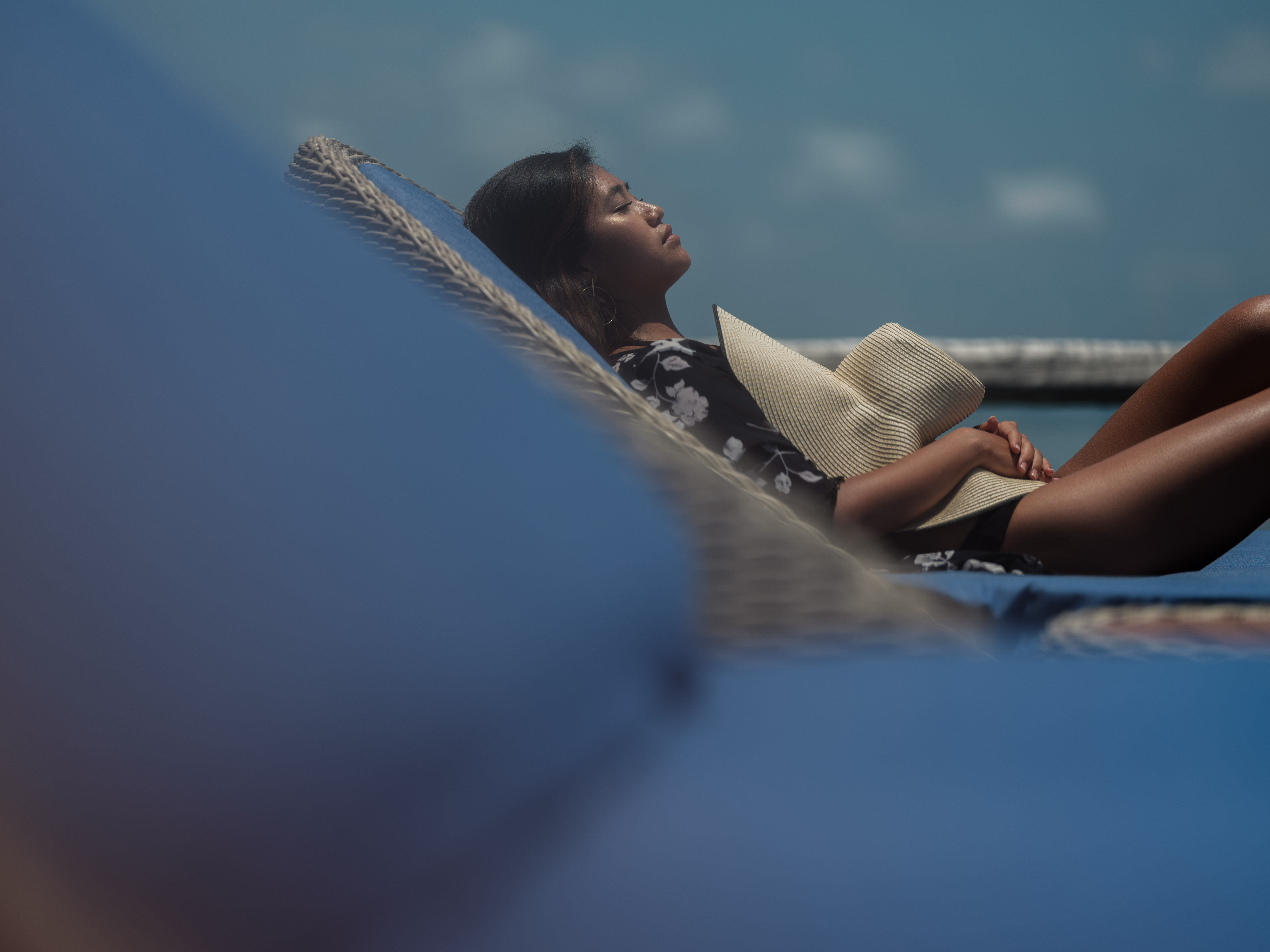 close_up_asian_girl_black_robe_holds_straw_hat_sun_bathing_on_blue_day_bed_overwater_suite
