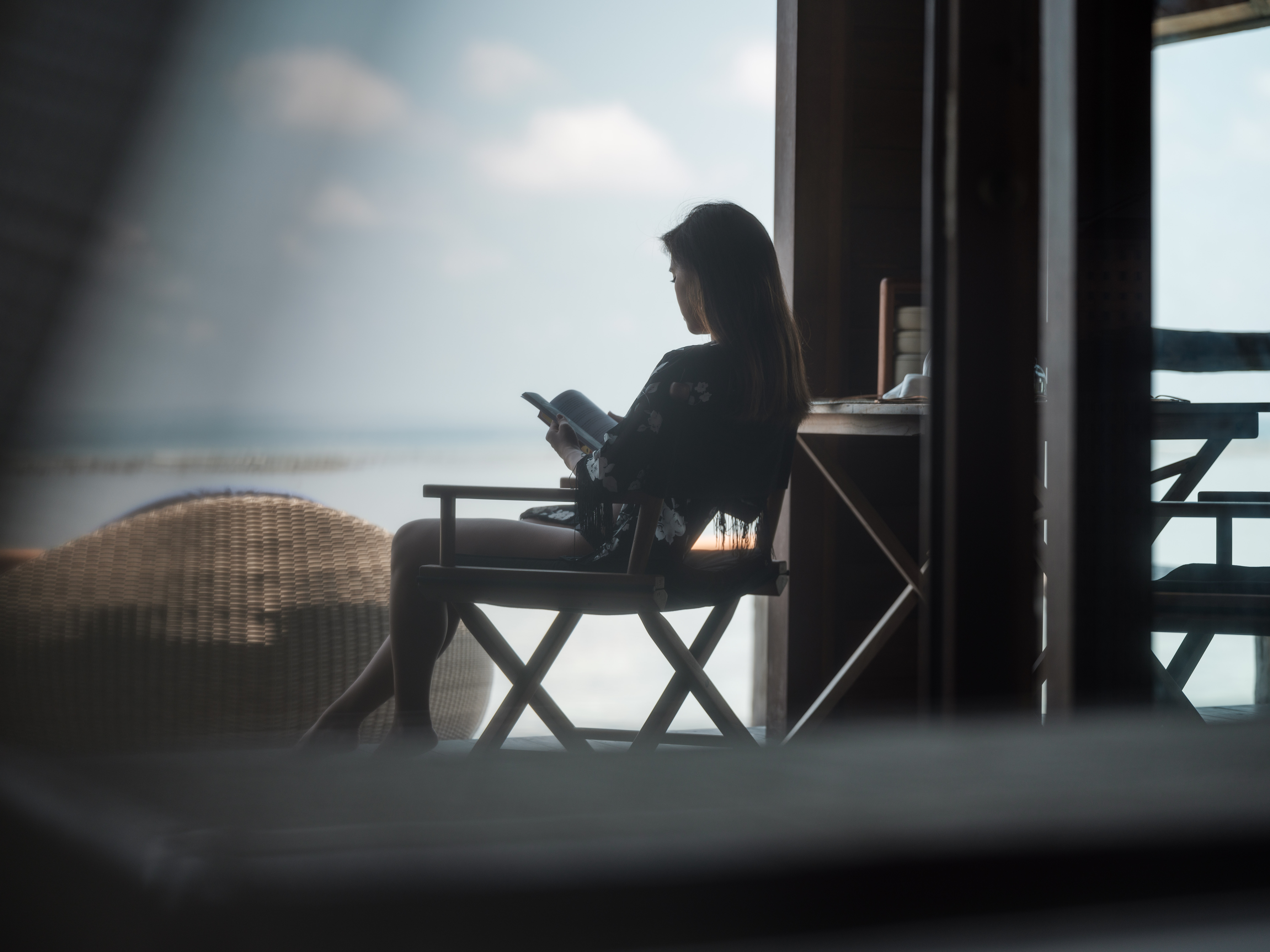 asian_girl_black_robe_on_arm_chair_reading_book_in_overwater_suite_blurred_lagoon_view