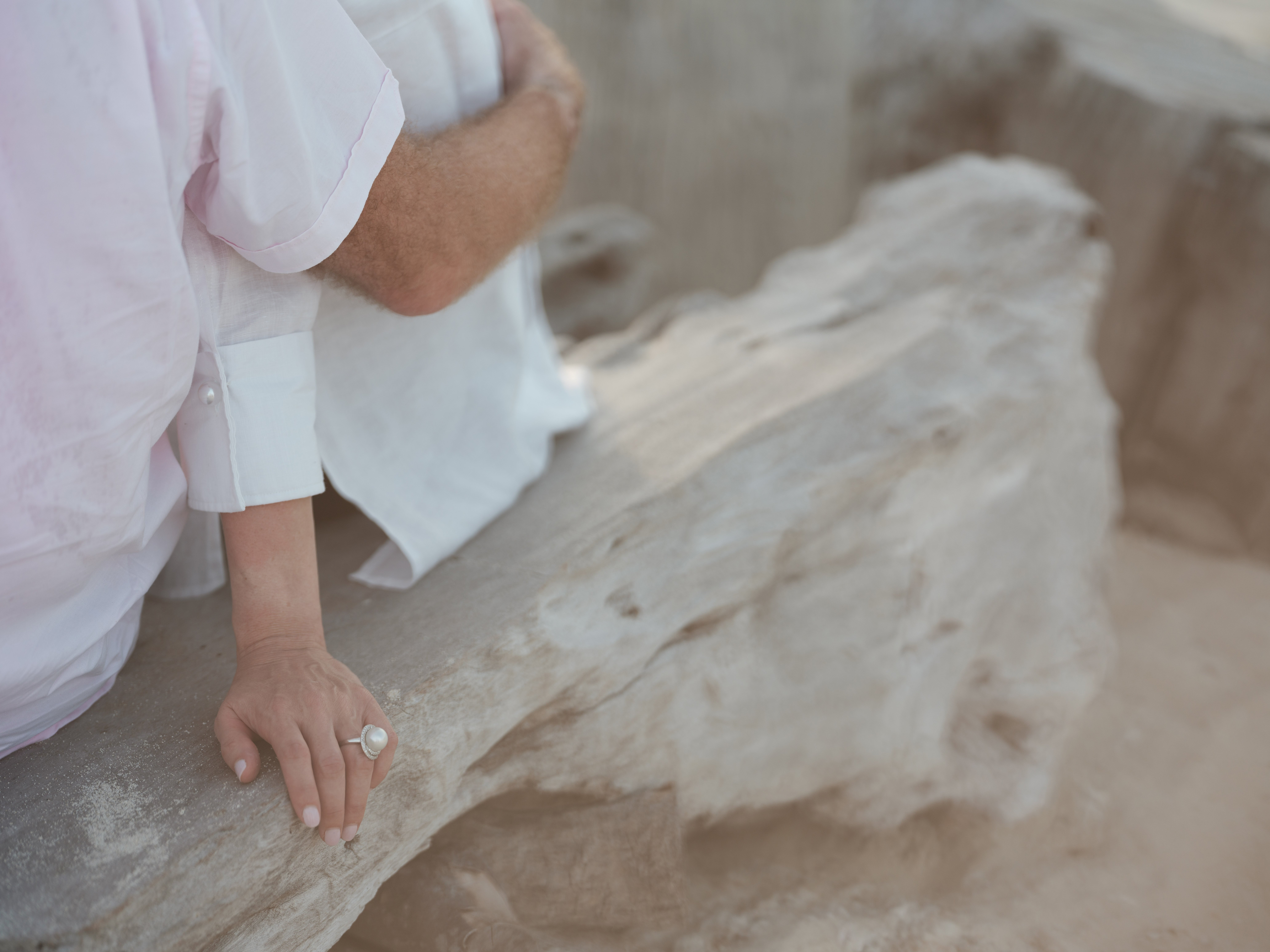 couple_sitting_woman_hand_pearl_ring_resting_on_beach_driftwood (4)