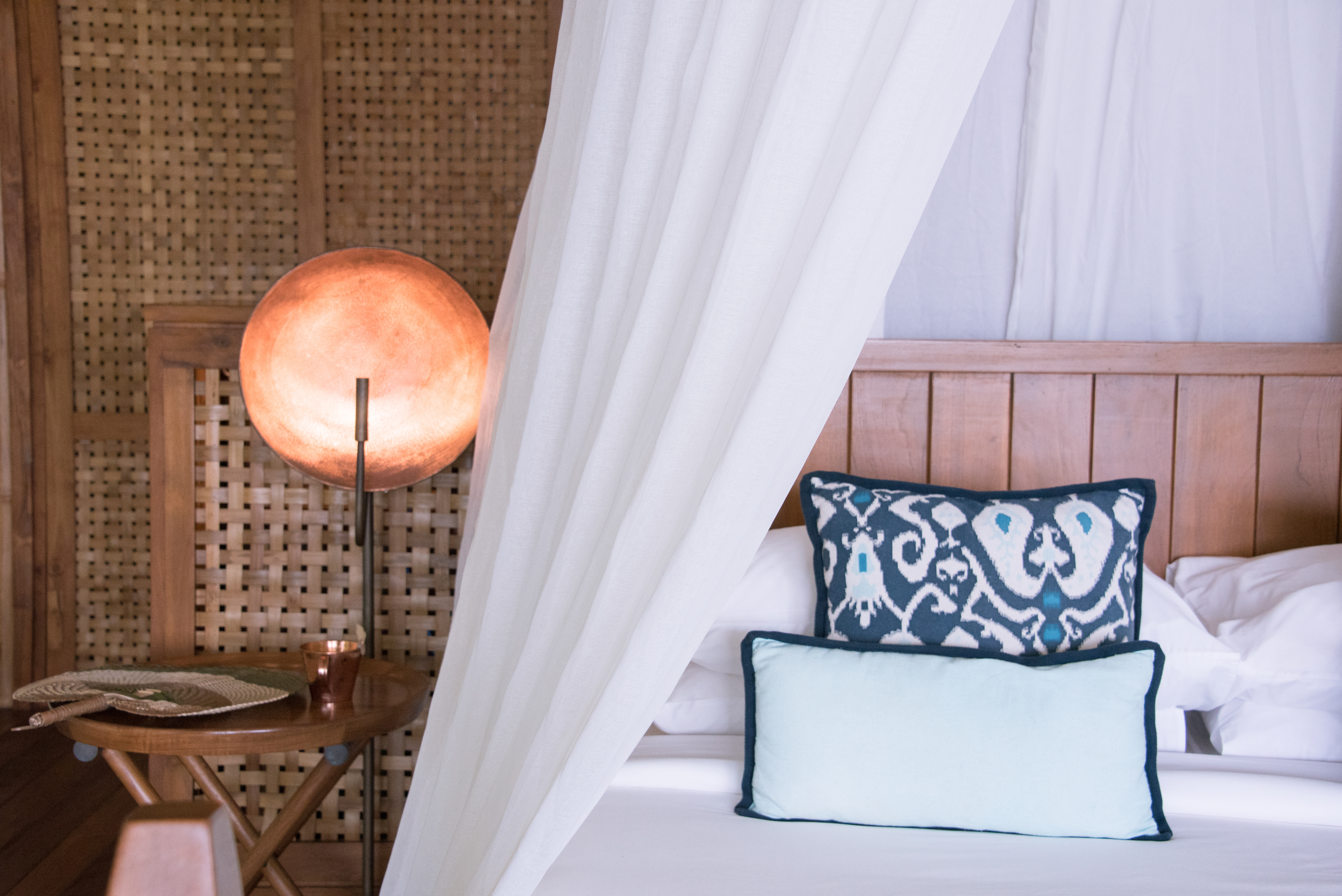 white_bed_canopy_with_cooper_bed_side_light_with_rattan_fan_on_table_beach_suite