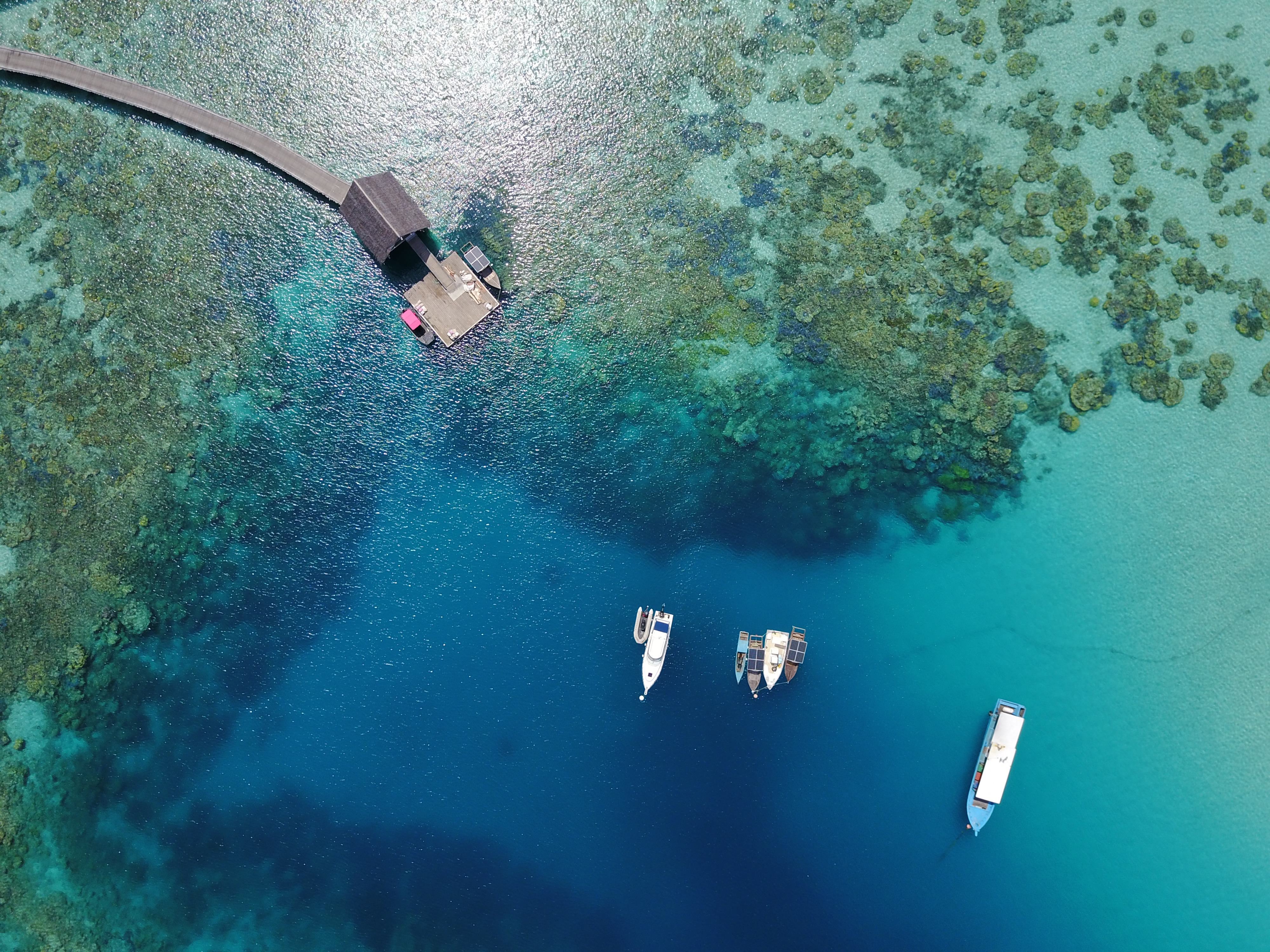 aerial_boats_in_coral_reefs_lagoon_jetty_thatched_roof (2)
