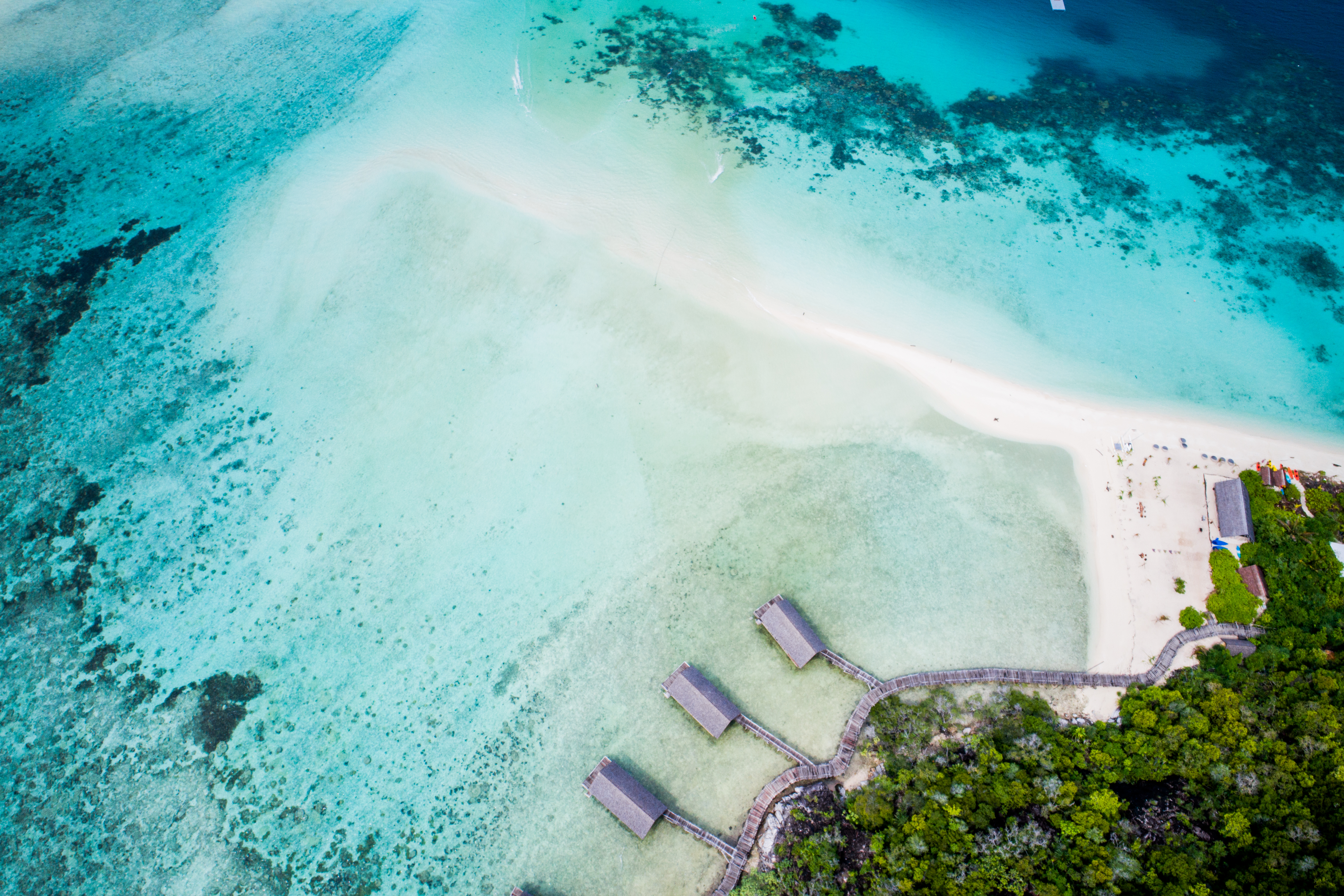 aerial_east_overwater_suites_boat_house_sandy_beach_green_forest_backgroundjpg
