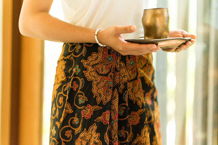 aura_female_staff_brown_black_indonesia_puppet_design_batik_skirt_hand_holding_welcome_tea_cup