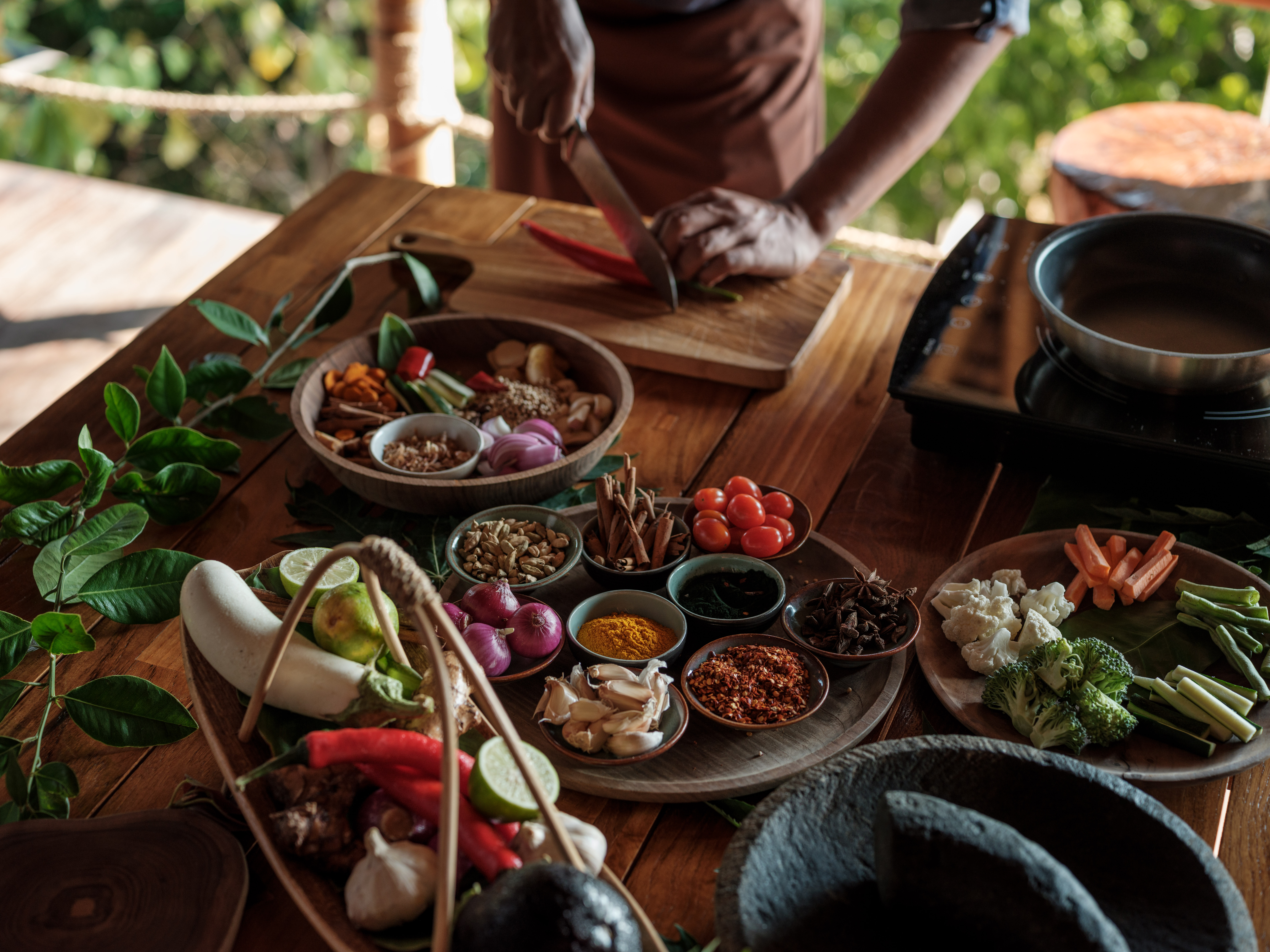 chef_teaching_cutting_red_chilli_fresh_ingredients_prepared_pestle_mortar_on_table_cooking_class