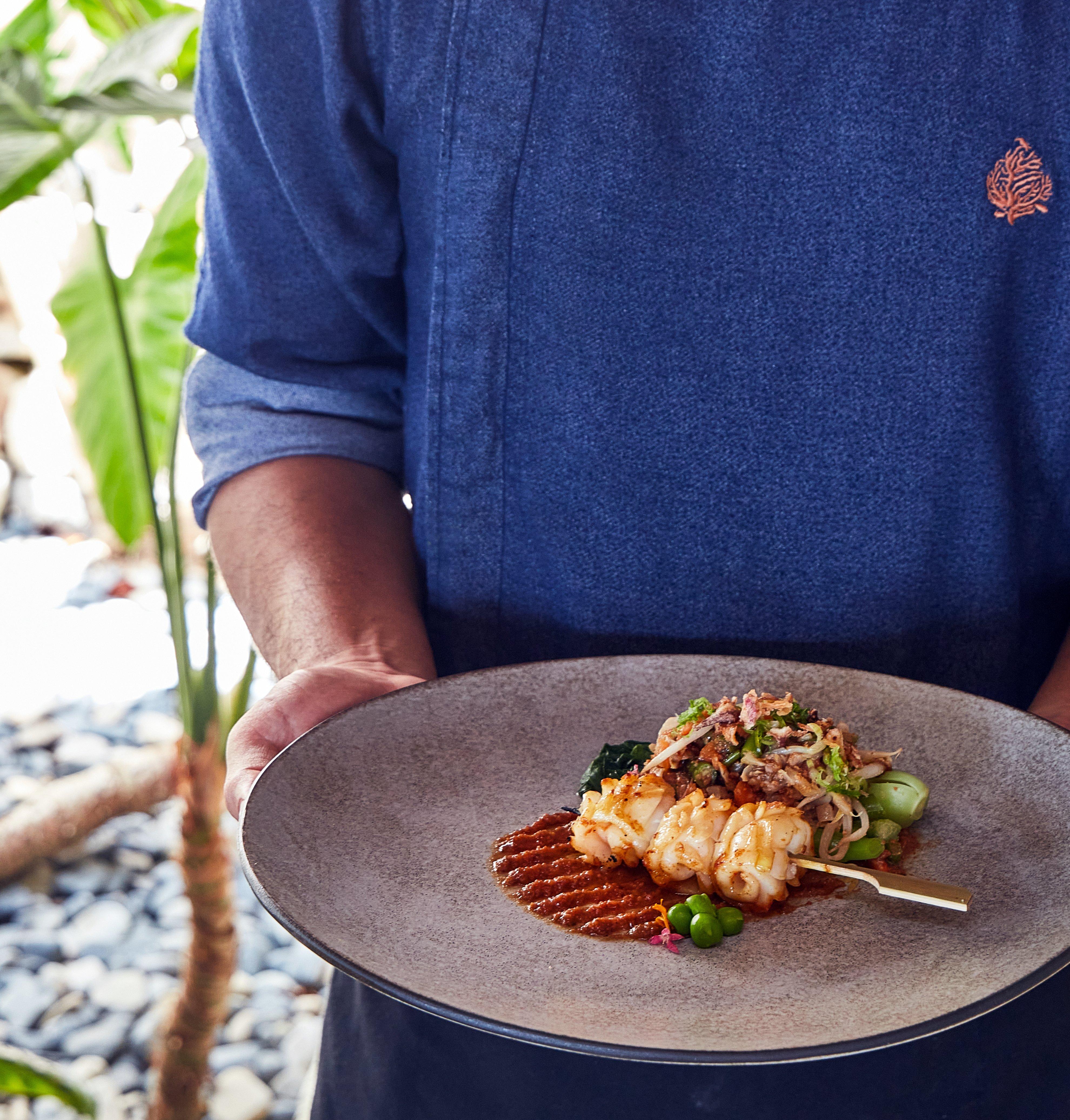 chef_wearing_bawah_uniform_holding_squid_skewer_with_peanut_sauce_and_gado_gado_treetops (2)