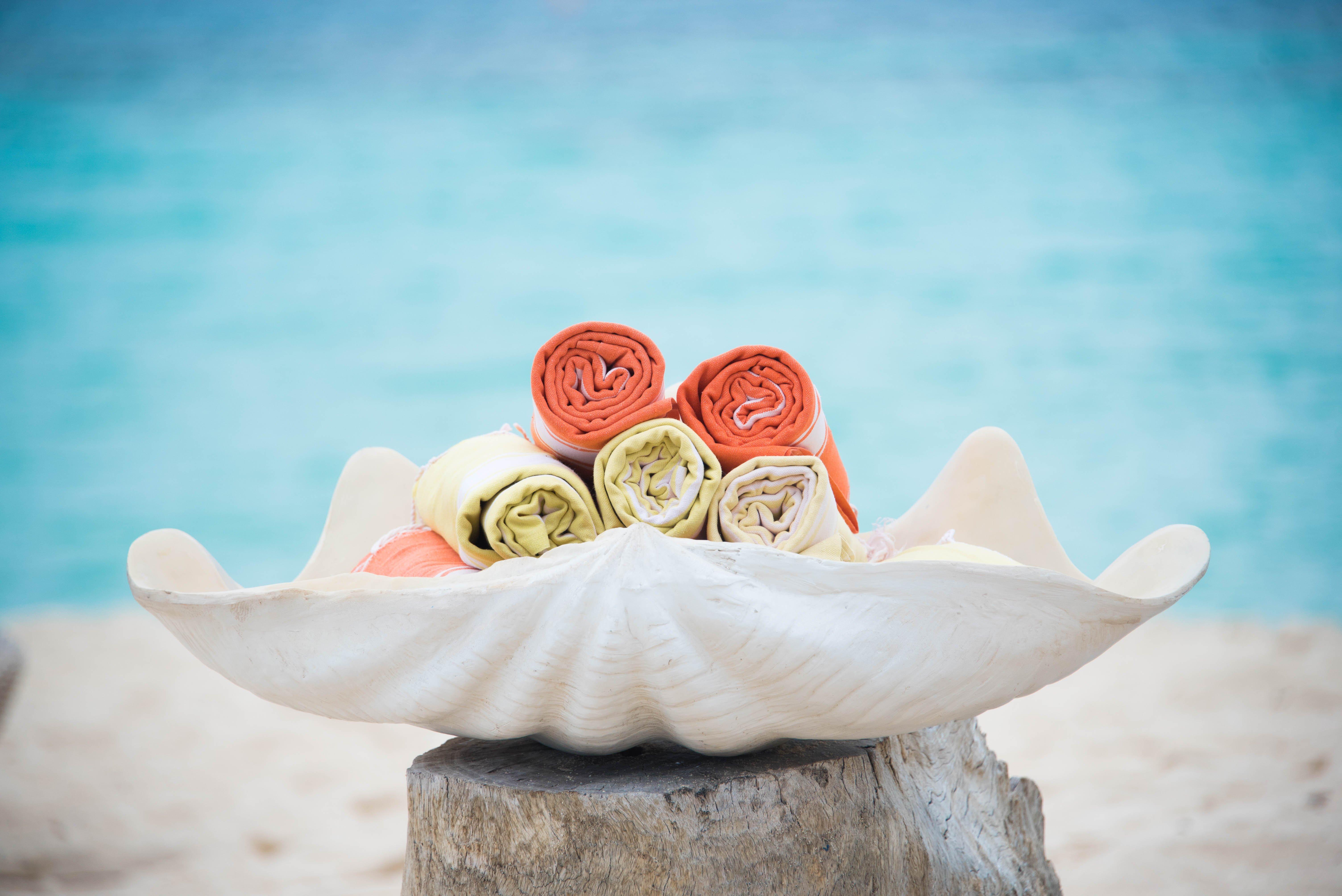 colourful_beach_towels_on_white_sea_shell_blurred_lagoon_background_boat_house