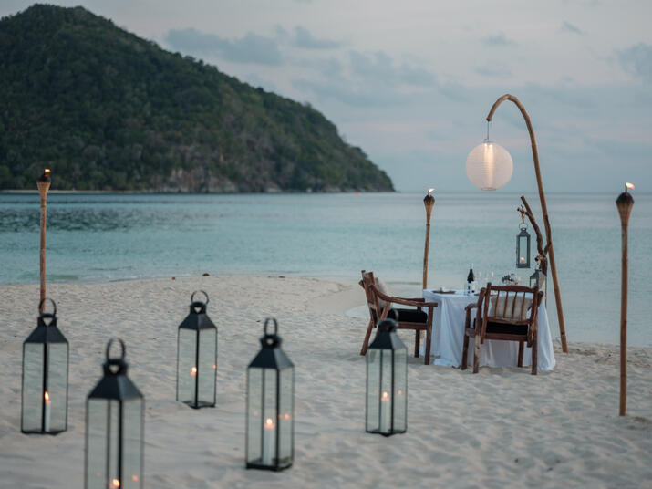 fire_torch_romantic_private_dinner_by_the_beach_wooden_arm_chairs_set_up_with_lit_candle_lanterns_sanggah_view