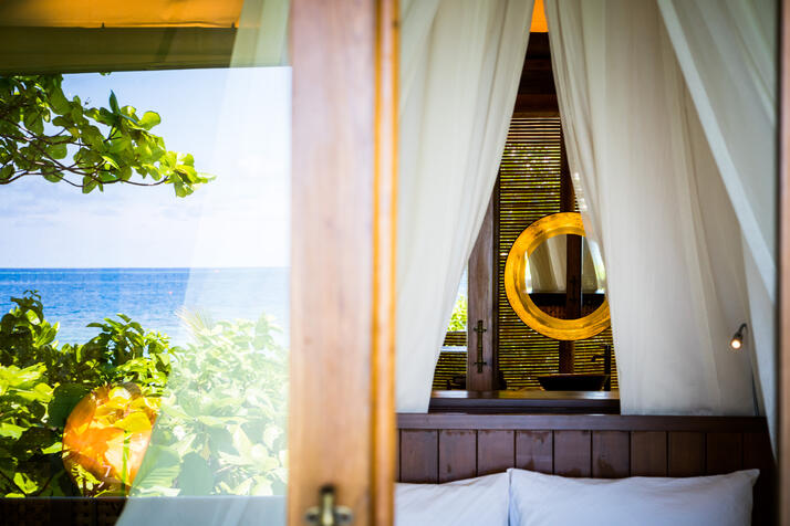 foliage_blue_lagoon_reflection_at_glass_door_beach_suite_with_lit_copper_mirrors_behind_canopy_bed