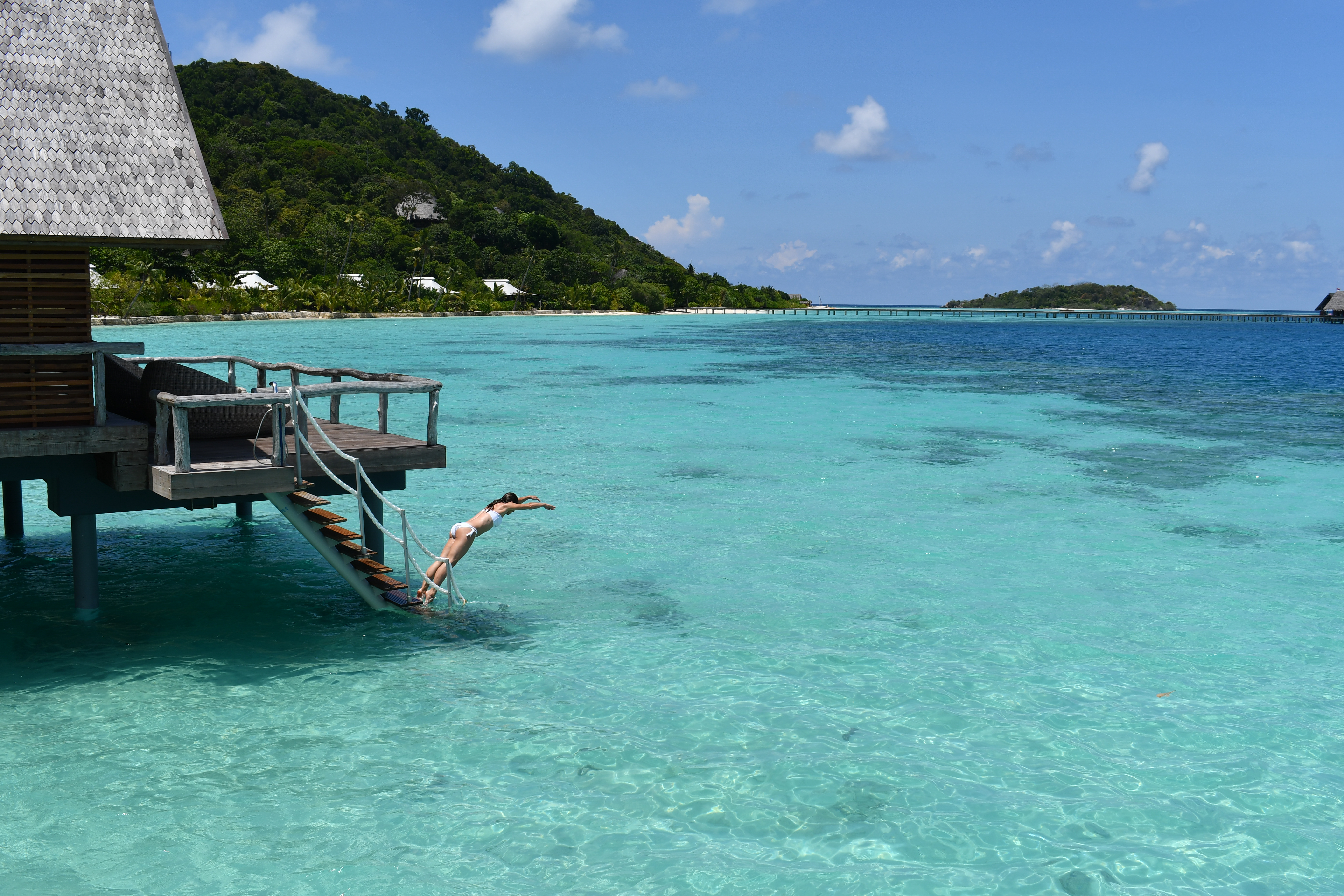 girl_in_white_bikini_jumping_in_to_lagoon_from_overwater_suite_stairs_with_jetty_view