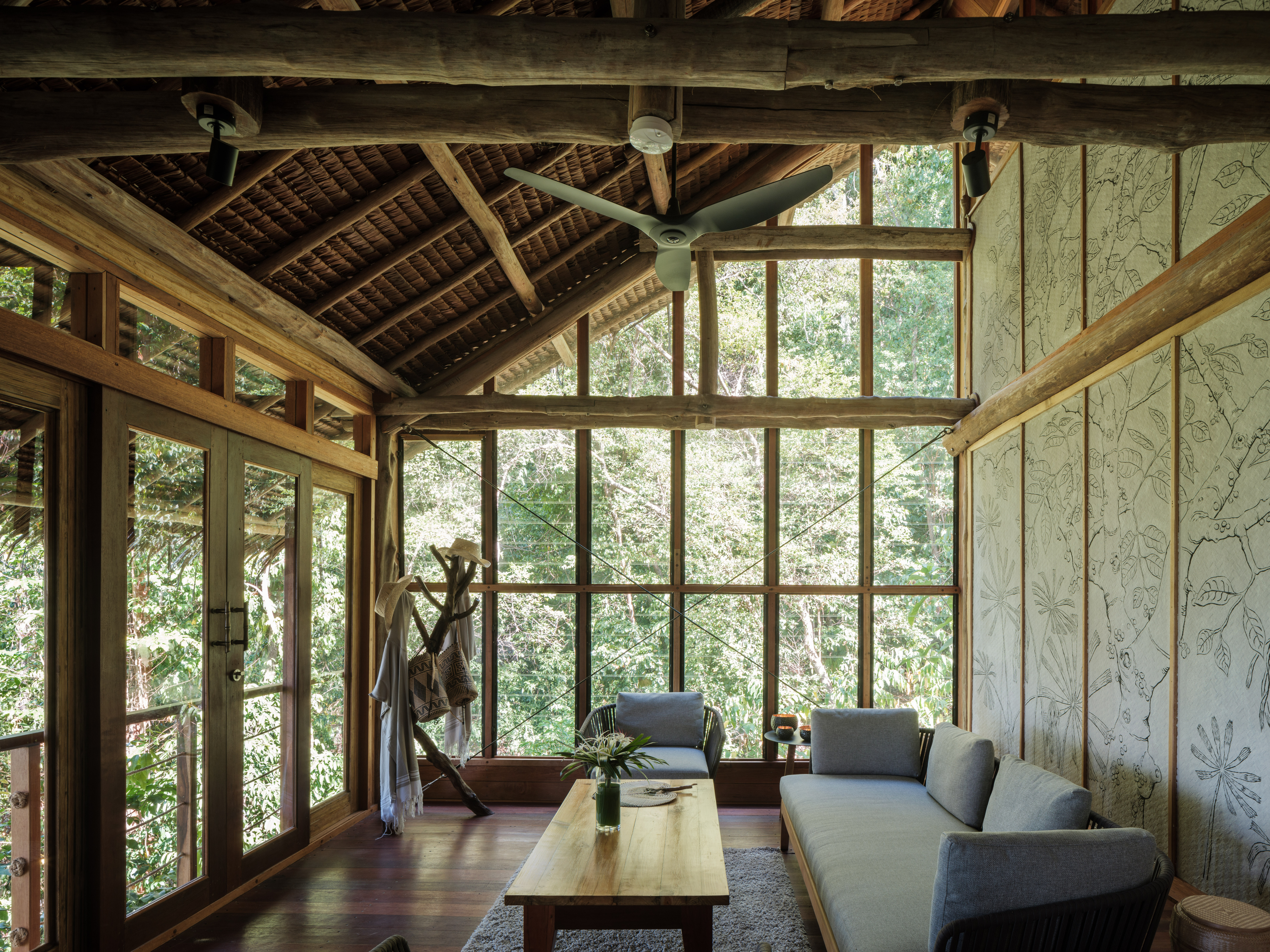 glass_window_foliage_view_on_living_lounge_with_straw_hat_beach_robes_wicker_bag_hanging_tree_branch_hooks_jungle_lodge