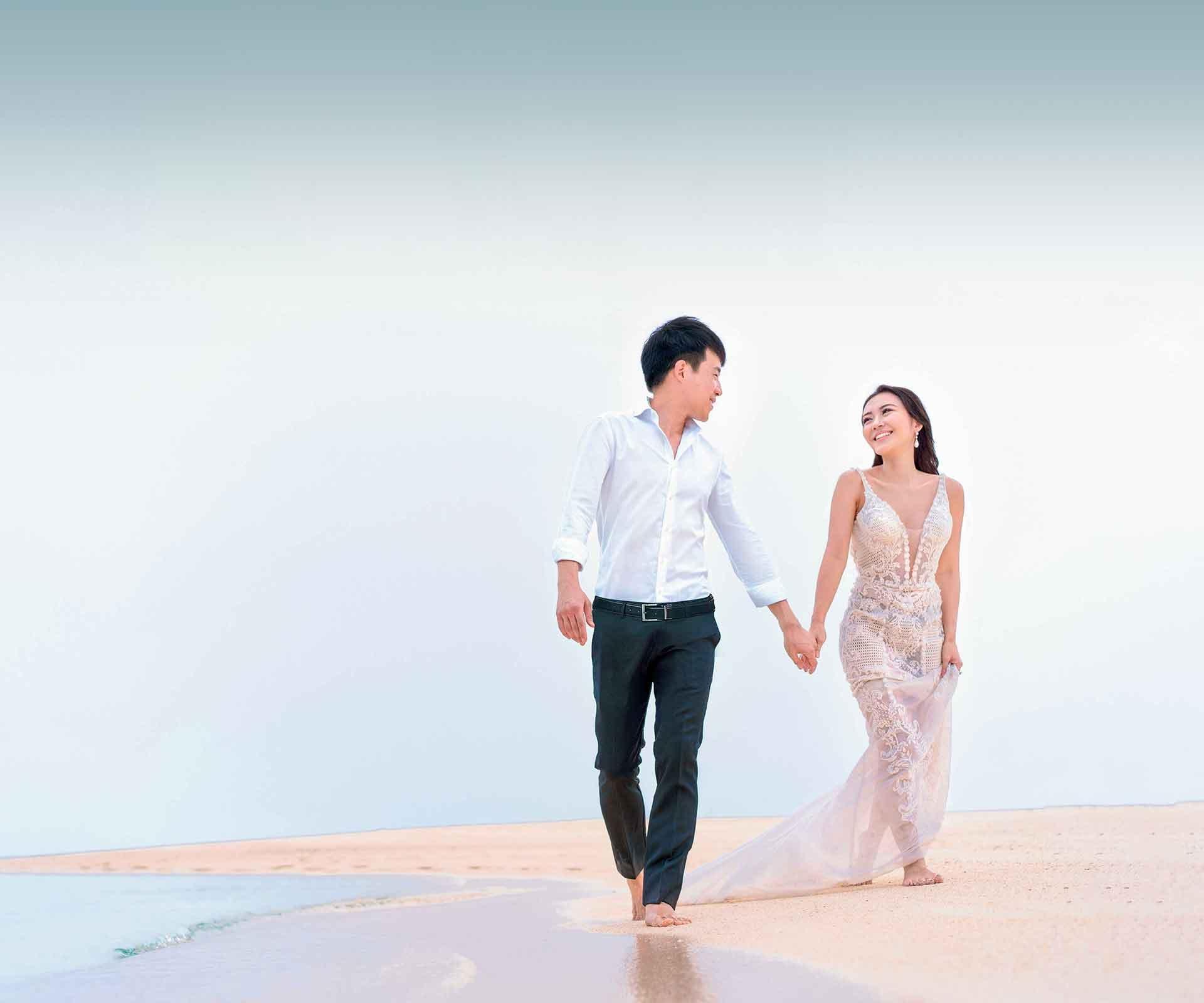 gradient_male_female_wedding_couple_walking_along_beach_pink_hour-3