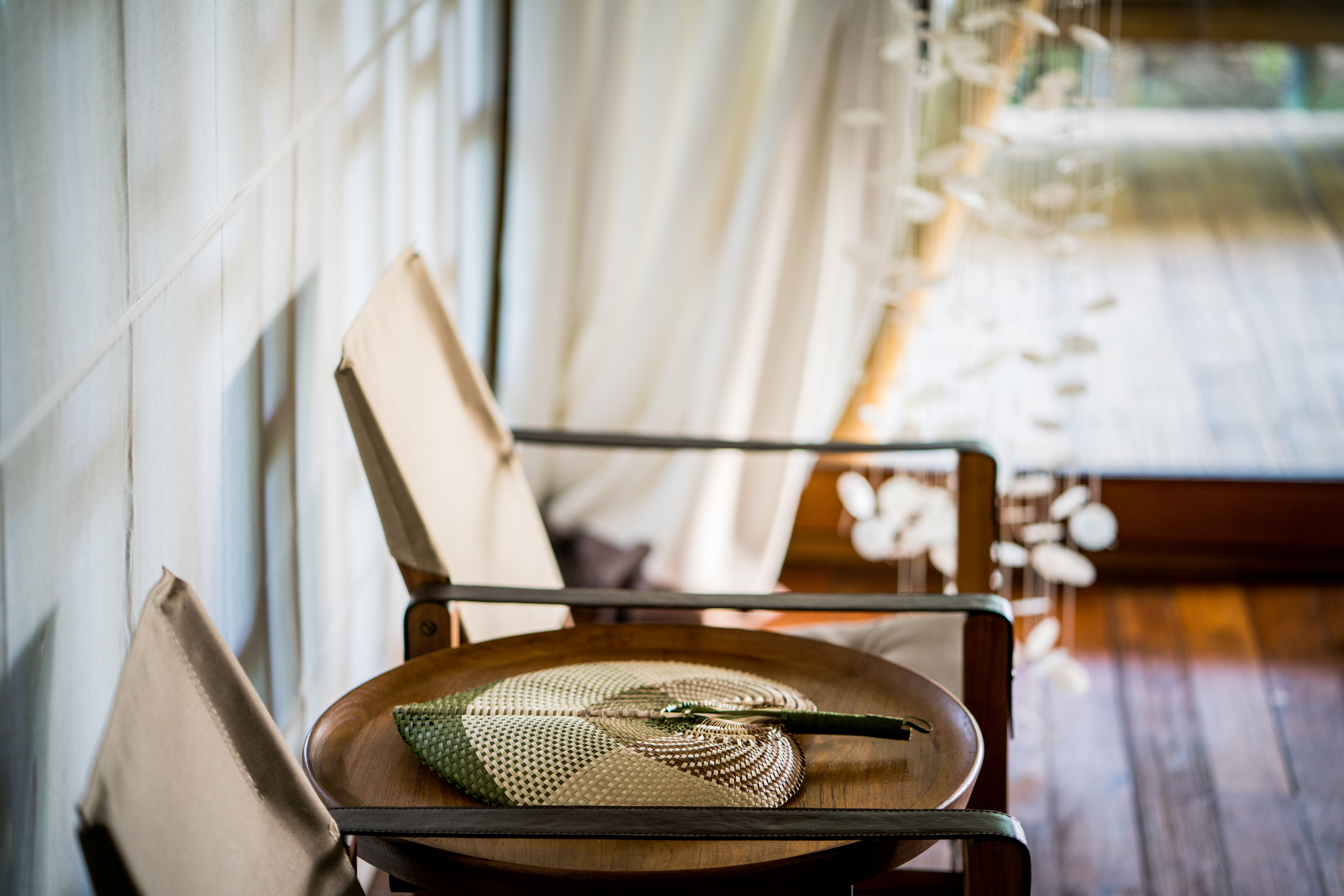 green_brown_rattan_hand_fan_on_wooden_table_arm_chairs_iwith_white_curtain_behind_blurred_jellyfish_tentacles_light_beach_suite
