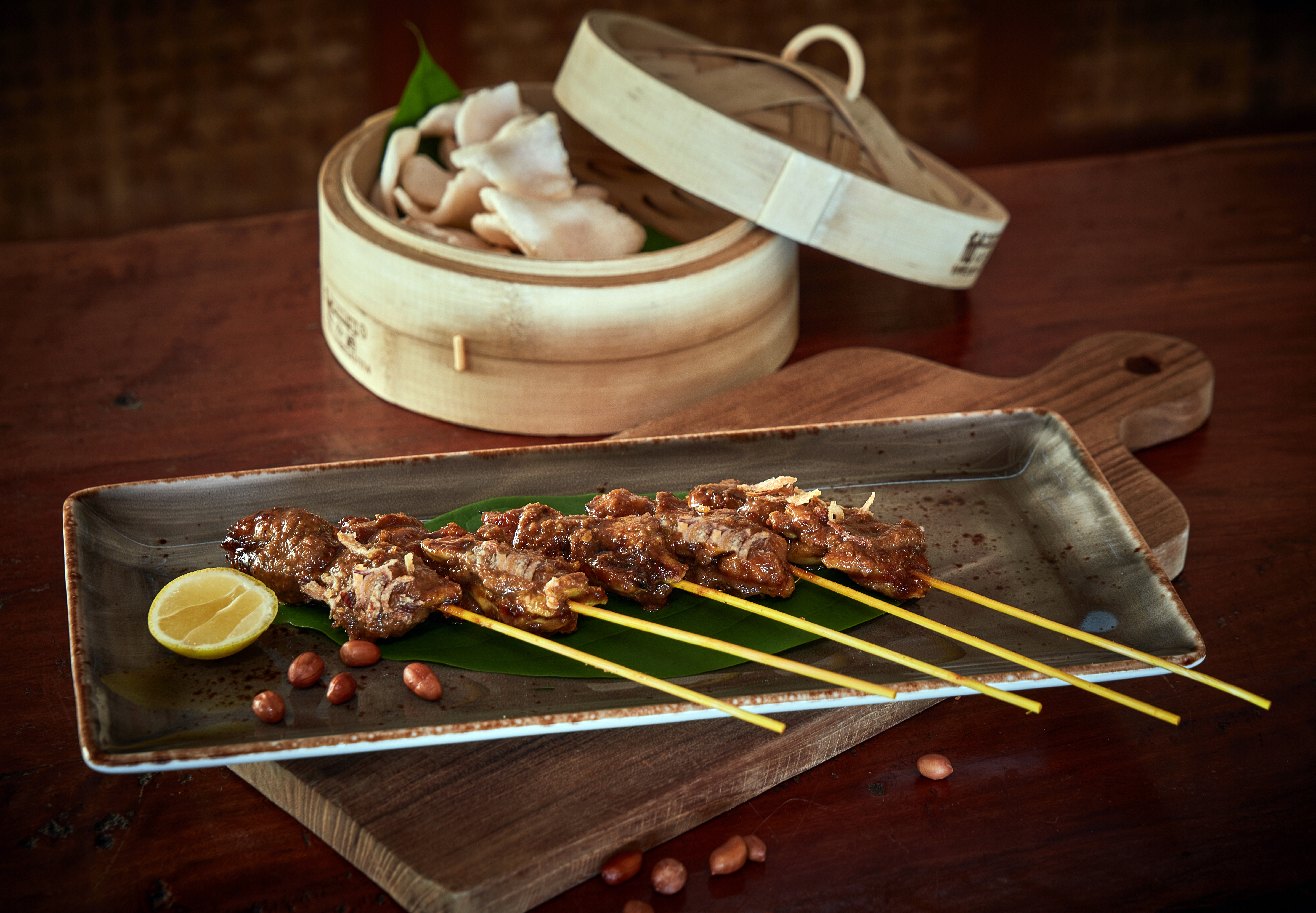 grilled_satay_served_with_roasted_peanuts_and_crackers_in_bamboo_steamer_treetops