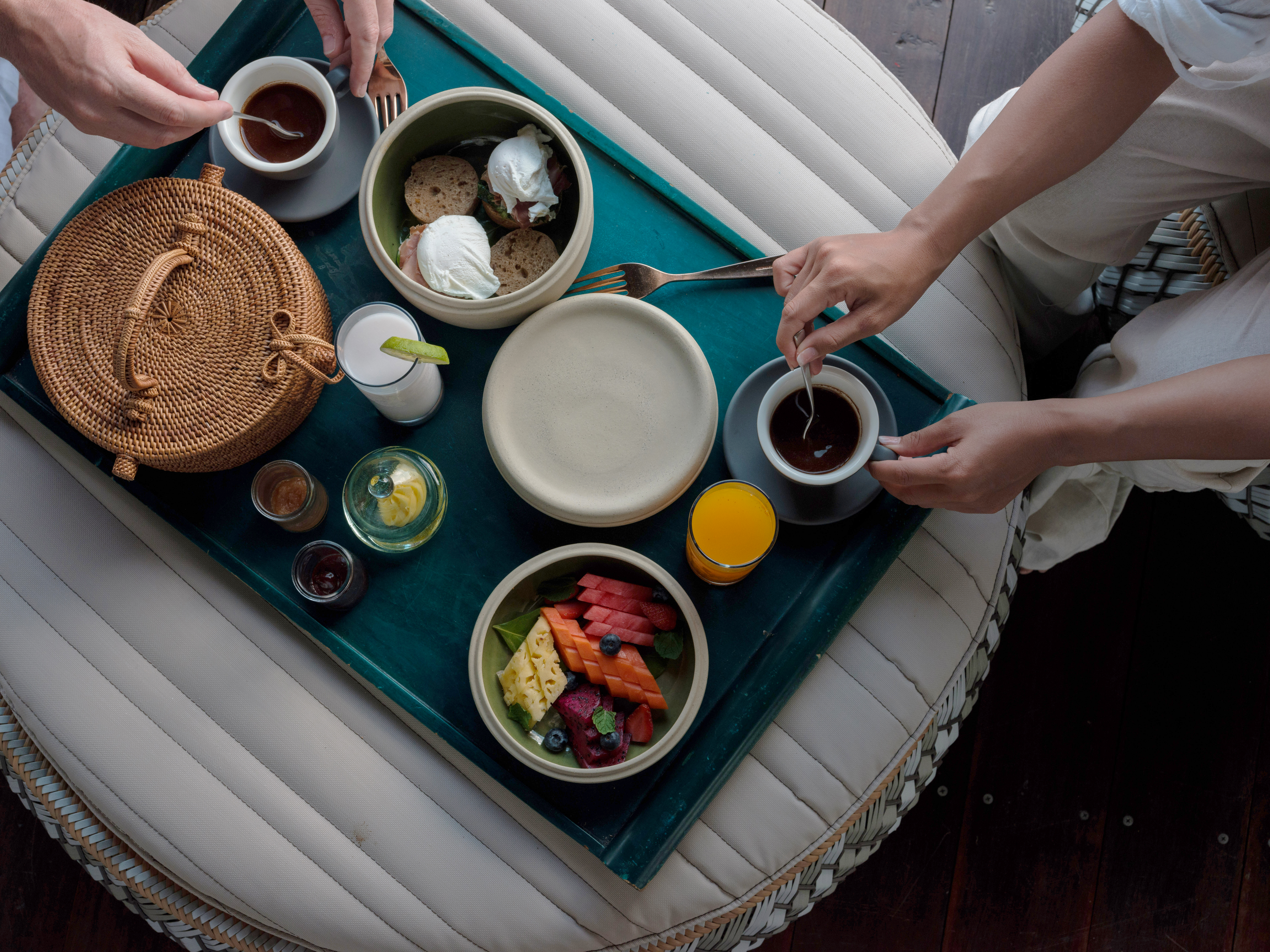 in_room_dining_breakfast_woven_basket_on_cushion_table_overwater_suite_from_above