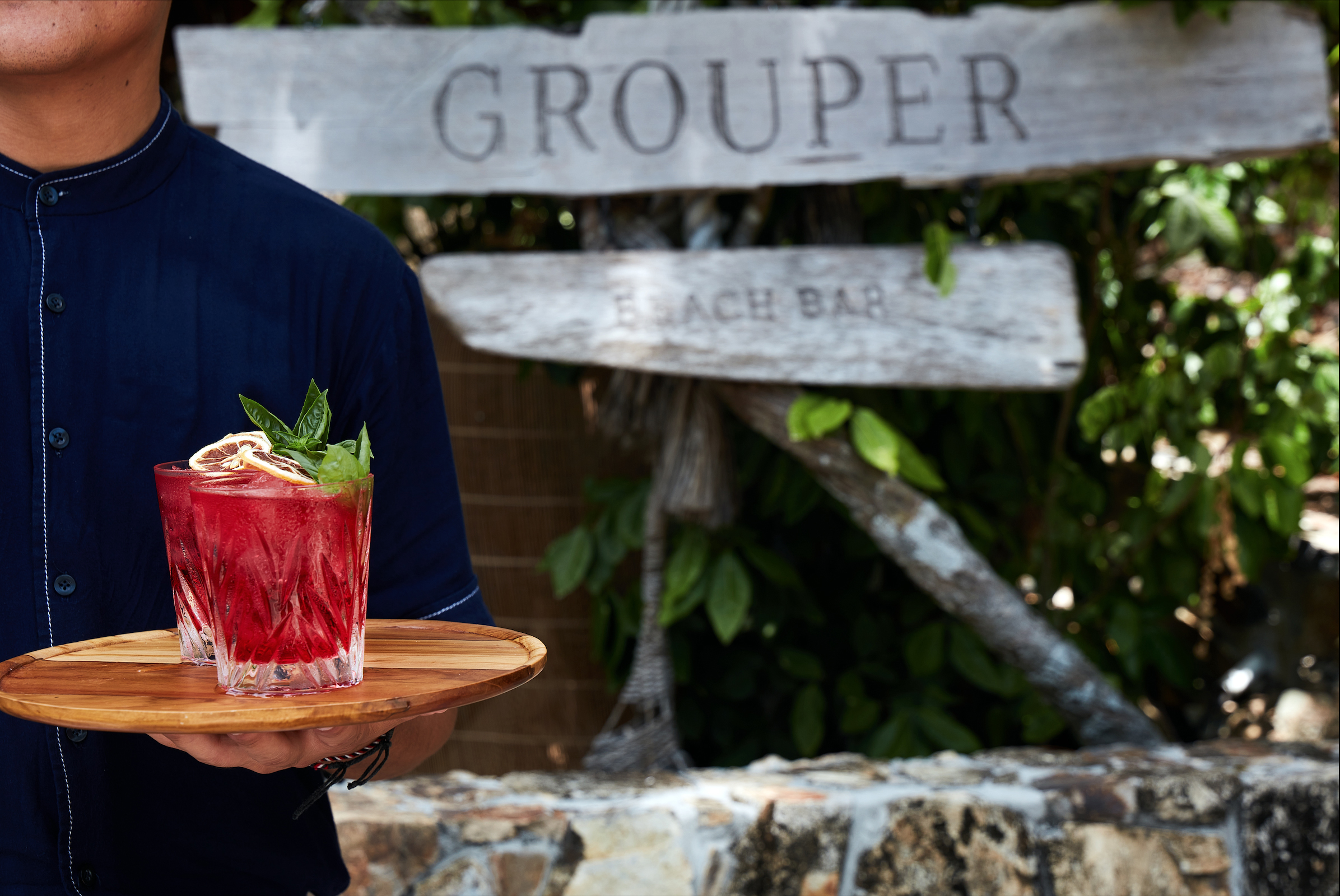 male_staff_holding_tray_with_red_cocktails_grouper_bar_sign_in_background_