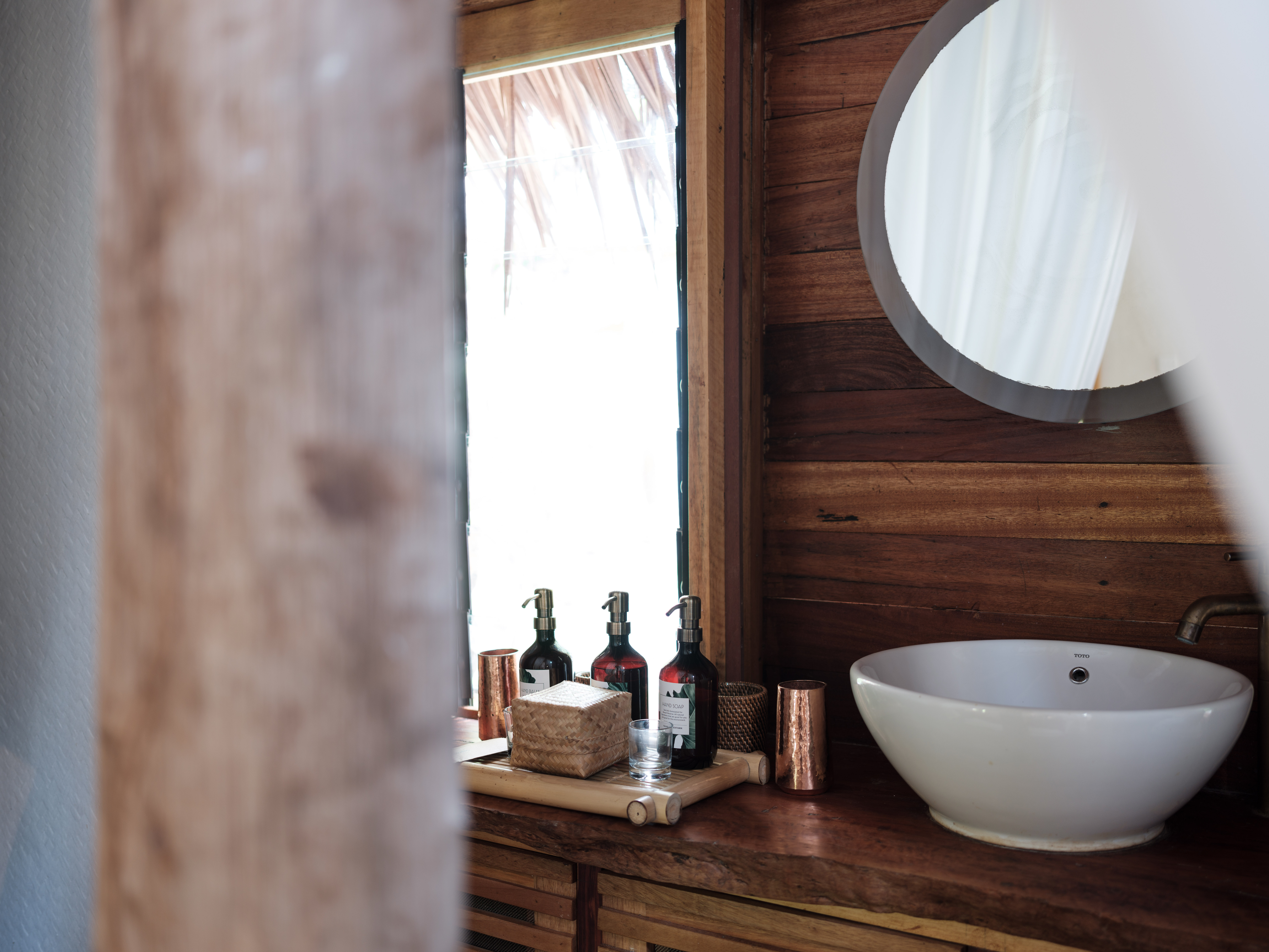 round_white_bathroom_mirrors_with_basin_soap_dispenser_bottles_jungle_lodge (1)