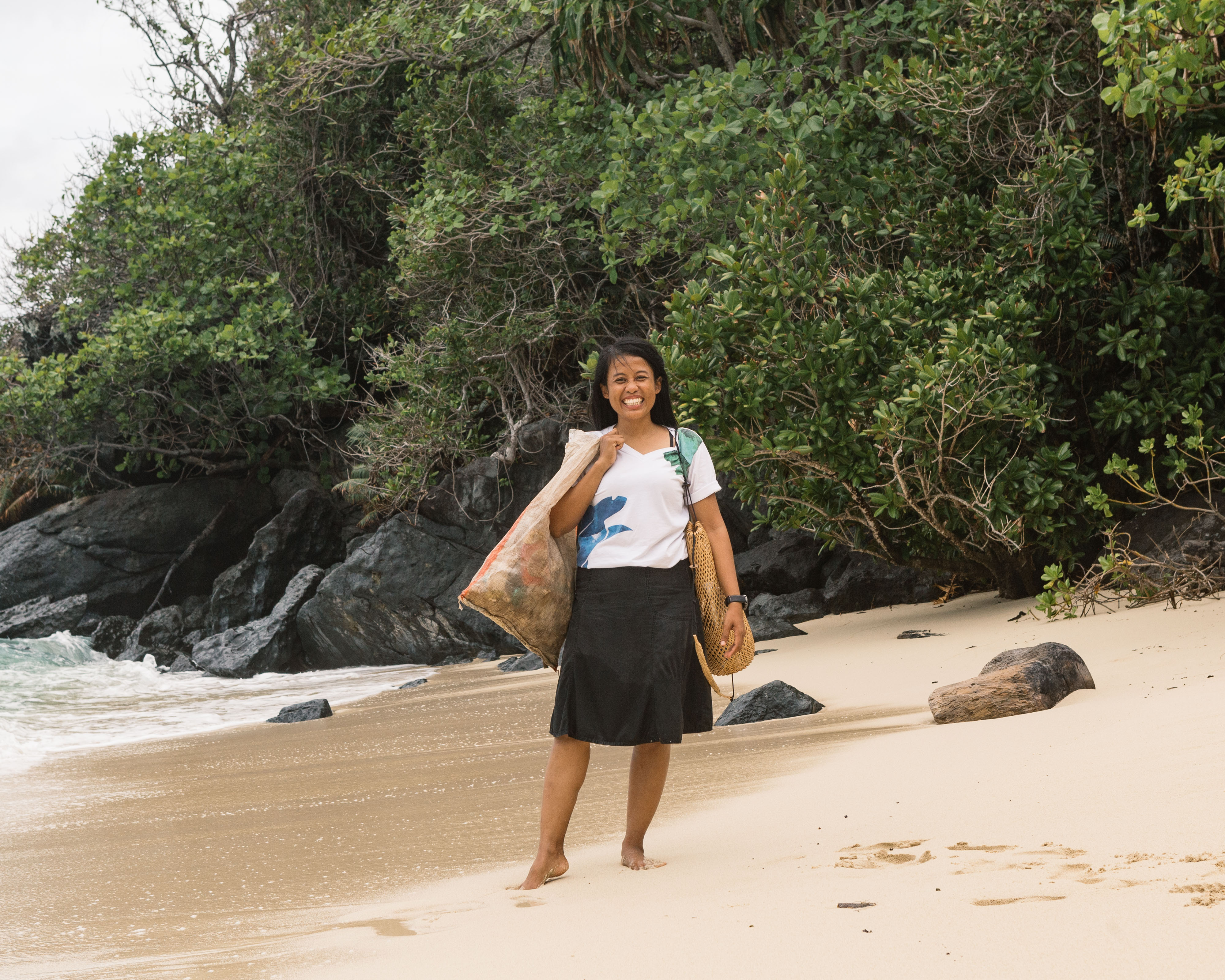 smiley_female_staff_collecting_trash_in_sack_beach_cleaning