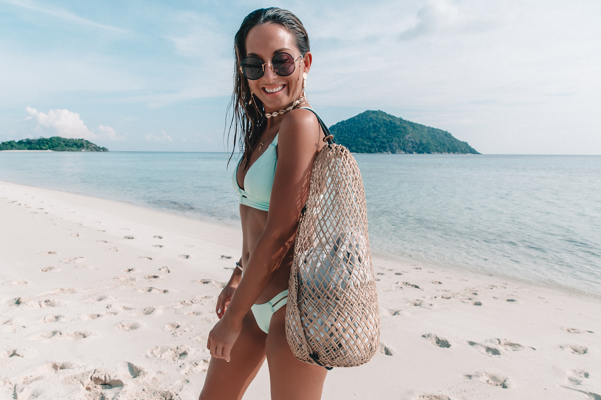 smiling_tanned_woman_sunglasses_holding_wicker_bag_looking_down_at_beach_sanggah_muerba_background