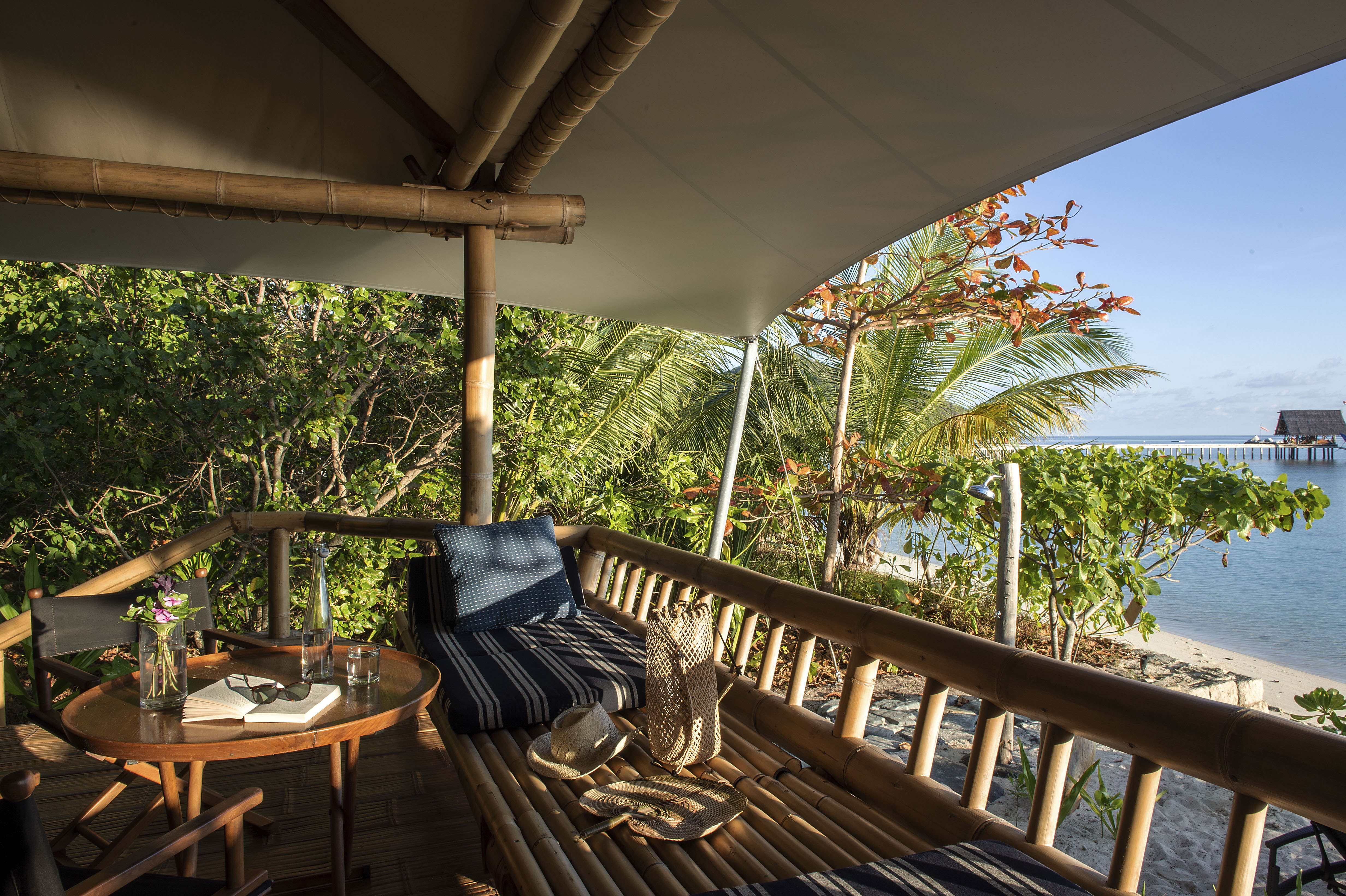 sunlight_into_straw_hat_wicker_bag_rattan_fan_on_bamboo_bench_side_arm_chairs_beach_suite_veranda_looking_out_jetty