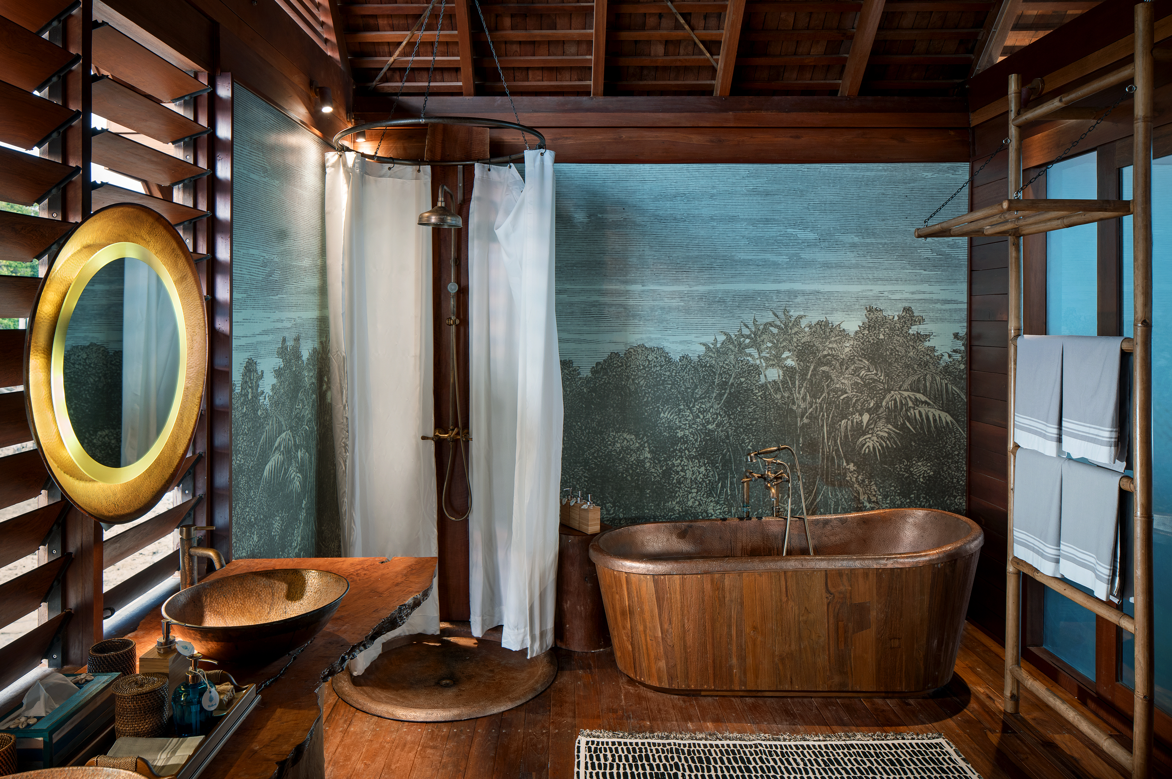 wall_painting_behind_copper_bath_tub_round_mirrors_overwater_suite_bathroom
