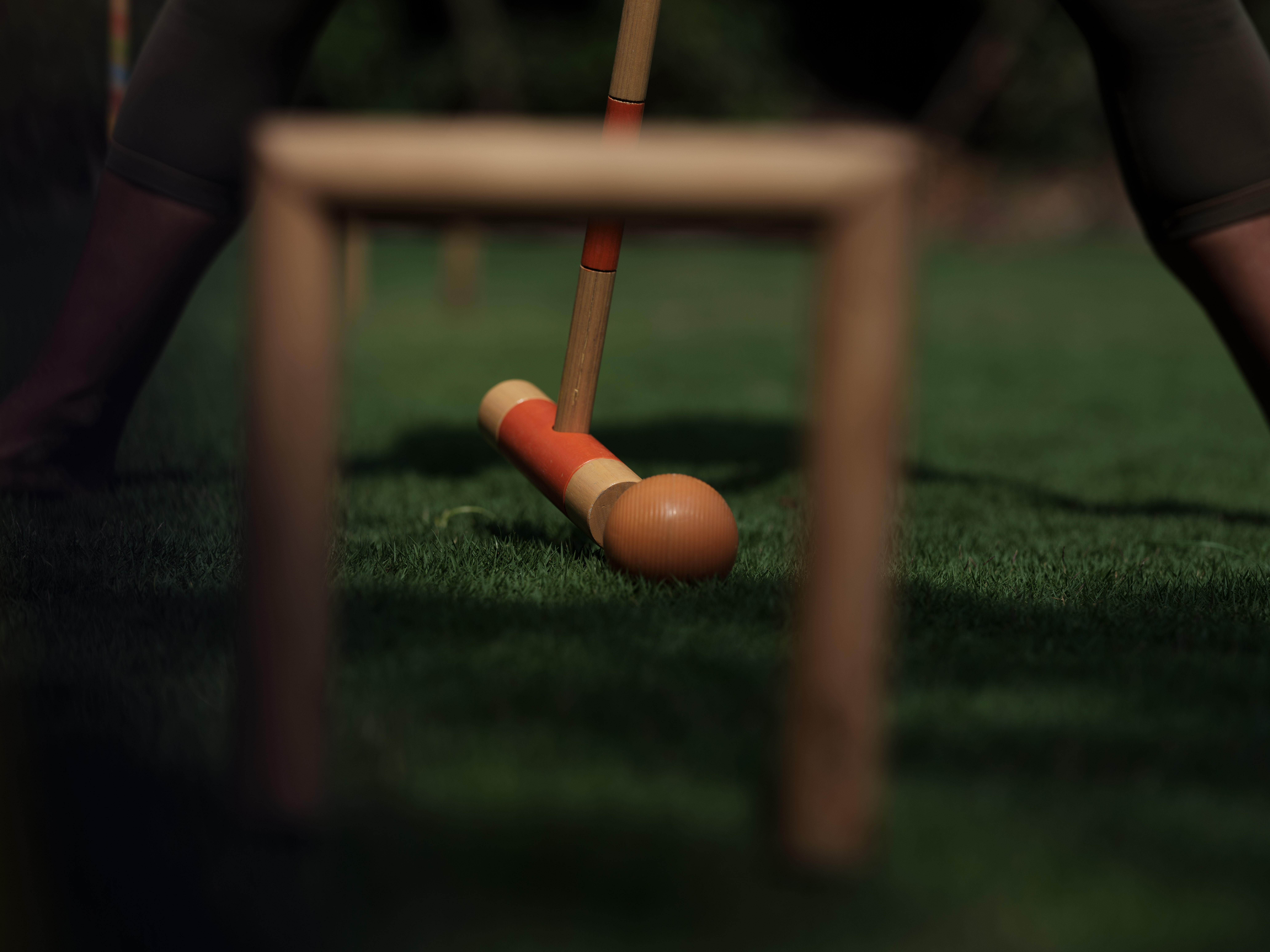 woman_hitting_orange_ball_with_wooden_mallet_in_grass