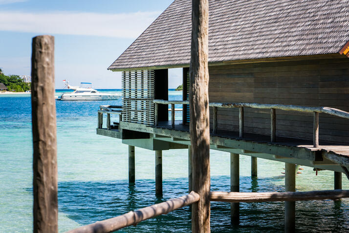 wood_banister_along_side_deck_overwater_suite_with_white_boat_in_lagoon_background